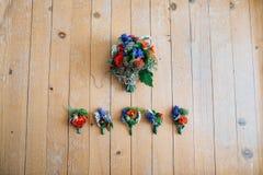 新娘花束和钮扣眼上插的花在一个木地板上 免版税库存照片