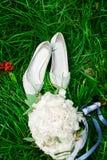 新娘花束和鞋子在草 免版税库存照片