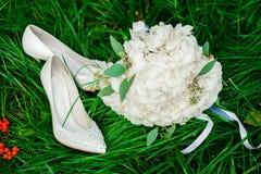 新娘花束和鞋子在草 图库摄影
