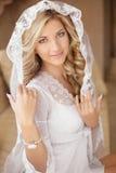 新娘面纱和婚礼礼服的美丽的微笑的新娘 beauvoir 免版税库存照片