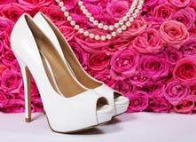 新娘鞋子和玫瑰。在流行粉红花的白色脚跟 库存照片