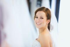 新娘:俏丽的妇女佩带的面纱在镜子看 免版税图库摄影