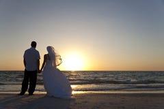 新娘&新郎已婚夫妇日落海滩婚礼 免版税图库摄影