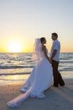 新娘&新郎已婚夫妇日落海滩婚礼 免版税库存图片