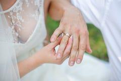 新娘戴着在新郎的手指的金子婚戒 免版税库存照片