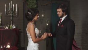 新娘戴着婚戒给新郎在有蜡烛的一个美妙的地点,恋人调查彼此的眼睛和 影视素材