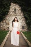 新娘 美丽的少妇在有花束的公园在一个温暖的夏日 免版税库存图片