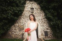 新娘 美丽的少妇在有花束的公园在一个温暖的夏日 库存照片