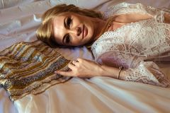 新娘` s早晨-白肤金发的少妇画象白色女用贴身内衣裤的有她的婚礼礼服的 免版税库存图片