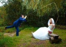 新娘cought她的一个新郎与一根钓鱼竿, 图库摄影