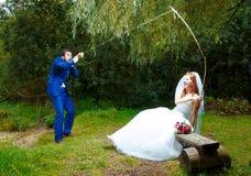 新娘cought她的一个新郎与一根钓鱼竿, 免版税库存照片