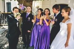 新婚佳偶与他们的朋友一起站立在步行期间  免版税库存照片