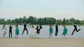 新婚佳偶加上跳跃在晴朗的海滩的女傧相和男傧相 股票视频