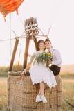 新婚佳偶势均力敌坐airballoon的篮子和观看在领域的日落 特写镜头 库存照片