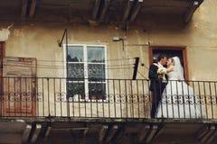 新婚佳偶在一个老半被破坏的阳台亲吻 免版税图库摄影