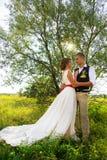 新婚佳偶在公园站立在阳光下,在树附近 婚姻本质上 免版税库存照片