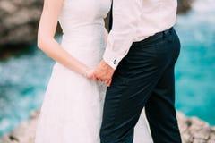 新婚佳偶在海附近握在岩石的手 夫妇holdi 免版税库存图片