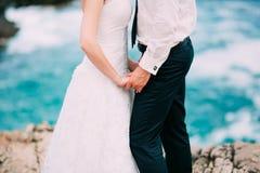 新婚佳偶在海附近握在岩石的手 夫妇holdi 图库摄影