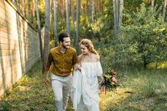 新婚佳偶在白礼服和人的森林女孩走一件橄榄色的衬衣的 土气婚礼 附庸风雅 免版税库存图片