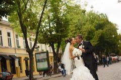 新婚佳偶在走的街道上亲吻 库存照片