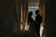 新婚佳偶婚礼之日 愉快的豪华站立在窗口的新娘和新郎在富有的屋子,嫩片刻里点燃 免版税库存图片