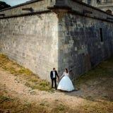 新婚佳偶握手,当站立在老巴洛克式的城堡的巨大的墙壁的时角落 库存照片