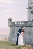 新婚佳偶新娘和新郎在美丽的巴洛克式的堡垒墙壁附近亲吻 在背景的壮观的天空视图 库存图片