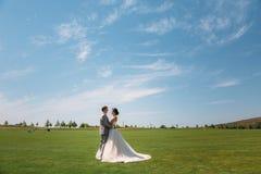 新婚佳偶沿高尔夫俱乐部的绿色领域走在一婚礼之日 西装的新郎是灰色的和 库存图片
