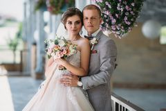 新婚佳偶画象在婚礼之日 一套灰色衣服的新郎与一件白色衬衣和蝶形领结拥抱一个美丽的新娘 免版税图库摄影