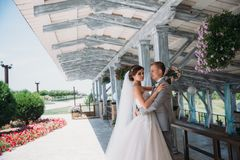 新婚佳偶画象在婚礼之日 一套灰色衣服的新郎与一件白色衬衣和蝶形领结拥抱一个美丽的新娘 库存照片