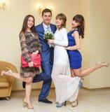 新婚佳偶的夫妇画象获得与女傧相的乐趣 图库摄影