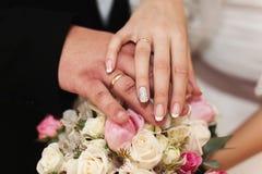 新婚佳偶的手有圆环的在婚礼花束 免版税库存照片