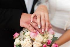 新婚佳偶的手有圆环的在婚礼花束 免版税库存图片