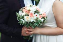 新婚佳偶的手有新娘特写镜头的花束的 婚姻概念 免版税库存图片