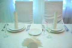 新婚佳偶的白色桌装饰在餐馆 背后照明 心脏布 免版税库存图片