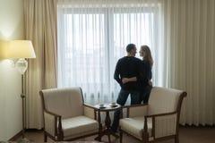 新婚佳偶站立在旅馆客房的窗口并且看彼此 年轻家庭是非常愉快的 库存图片