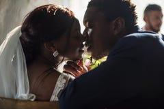 新婚佳偶非裔新娘亲吻的新郎婚礼庆祝 库存图片