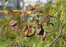 新婚的公园 两只咕咕叫的鸟和新娘和新郎挂锁在加工铁背面换下场,永恒爱的标志 免版税库存照片