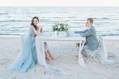 新婚的夫妇吃晚餐由海 库存图片