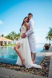 新婚的夫妇在婚姻以后在豪华旅游胜地 浪漫新娘和新郎松弛近的游泳池 蜜月 库存图片