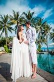 新婚的夫妇在婚姻以后在豪华旅游胜地 浪漫新娘和新郎松弛近的游泳池 蜜月 免版税库存图片