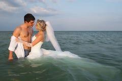 新婚的夫妇游泳在海 免版税库存图片