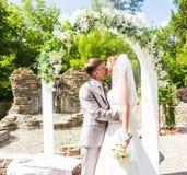新婚的夫妇第一个亲吻在婚礼下的成拱形 免版税图库摄影