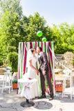新婚的夫妇第一个亲吻在婚礼下的成拱形 库存照片