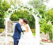 新婚的夫妇第一个亲吻在婚礼下的成拱形 免版税库存照片