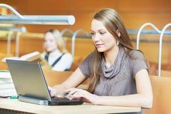 新学员女孩与膝上型计算机一起使用在图书馆里 免版税库存照片