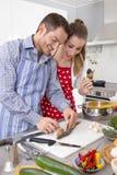 年轻新已婚夫妇在一起烹调新鲜的厨房里 免版税库存照片