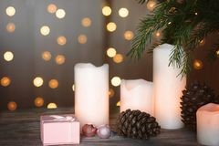 新年与被点燃的蜡烛、爆沸和一件礼物的` s静物画在圣诞树旁边的一个箱子和诗歌选在背景中 库存图片