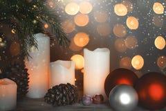 新年与被点燃的蜡烛、锥体和欢乐球在圣诞树旁边和诗歌选的` s静物画在背景中 免版税图库摄影