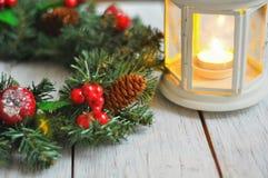 新年从一根冷杉木的` s花圈在白色木背景和一个蜡烛在一个白色烛台 免版税图库摄影